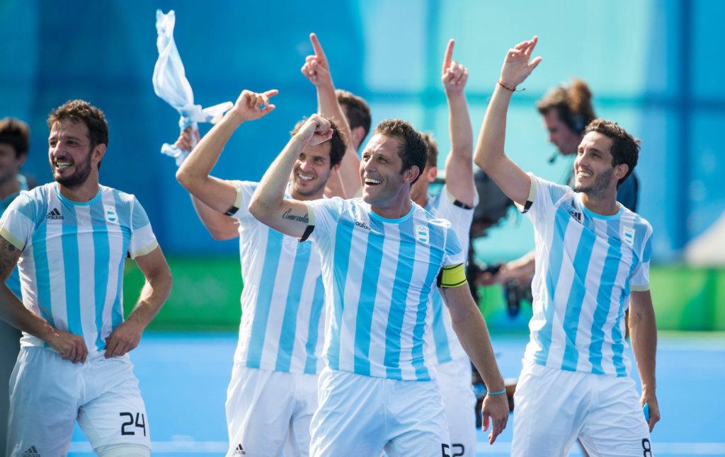 RIO DE JANEIRO - Celebrating Argentin players after the semifinal men Argentina-Germany (5-2). Pedro Ibarra (Arg) (m), left Manuel Brunet (Arg) and right Lucas Rey (Arg) . COPYRIGHT KOEN SUYK