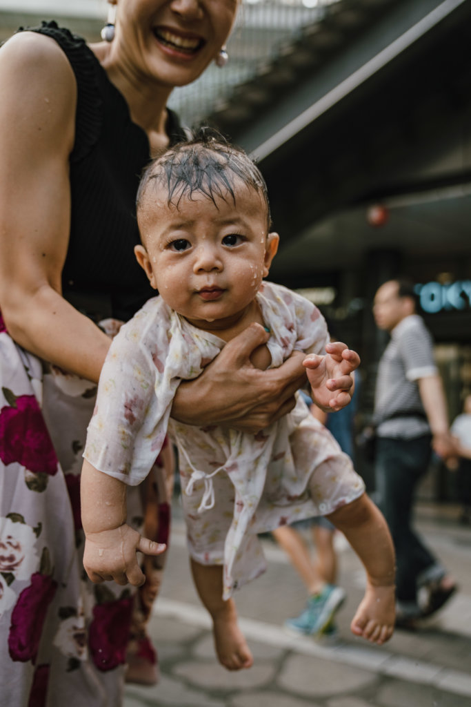 Ouders zoeken met hun kinderen verkoeling in Tokio - Foto: Anne Veenendaal